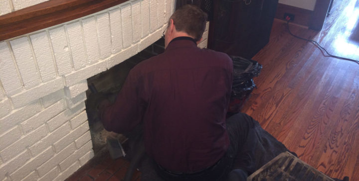 Our chimney technician cleaning a fireplace in Scarborough